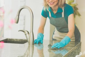 Woman Cleaning Kitchen Counter with Gloves and Sponge